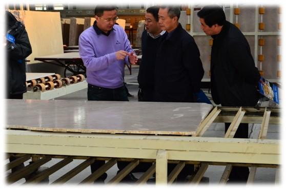 鑫磊矿业董事长邱华成(左一)向调研组介绍车间加工流程